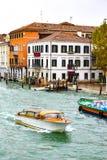 Wassertaxi und ein Boot, welches die Waren, segelnd durch Grand Canal in Venedig, Italien transportiert lizenzfreie stockfotos