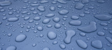 Wassertröpfchen auf blauem Auto Stockfoto