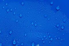 Wassertröpfchen auf einem blauen Plastik. Stockbild