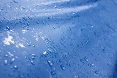 Wassertröpfchen auf einer blauen Plane Stockfotografie