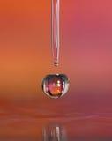 Wassertröpfchen in einer rosafarbenen und orange Umgebung. Stockfotografie