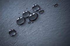 Wassertropfen über schwarzem Leder Stockfoto