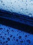 Wassertropfen auf Blau Stockfotografie