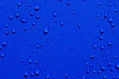 Wassertropfen auf blauem Gewebe Stockfotografie