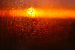 Wassertropfen auf einem Fensterglas nach dem Regen Der Himmel mit Wolken und Sonne auf Hintergrund Lizenzfreie Stockbilder