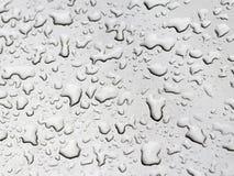 Wassertropfen auf einem grauen Auto stockbilder