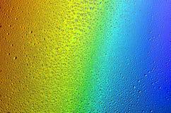 Wassertropfen auf einem Regenbogenhintergrund Lizenzfreie Stockbilder