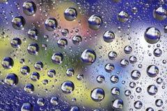 Wassertropfen auf Farbhintergrund Lizenzfreie Stockbilder