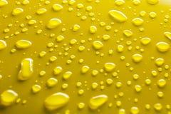 Wassertropfen auf Gelb Lizenzfreies Stockfoto