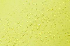 Wassertropfen auf gelbem Hintergrund Lizenzfreie Stockfotografie