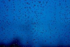 Wassertropfen auf Glas in der Unschärfe des Stadthintergrundes Stockfoto