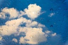 Wassertropfen auf Glasfenster über blauem Himmel Stockfotografie