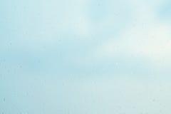 Wassertropfen auf Glasfenster über blauem Himmel Lizenzfreies Stockfoto