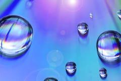 Wassertropfen auf Mehrfarbenhintergrund Lizenzfreies Stockfoto
