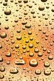 Wassertropfen auf orange Glas Lizenzfreie Stockfotografie