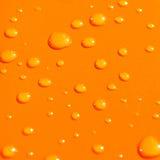 Wassertropfen auf orange Metallba Stockfoto