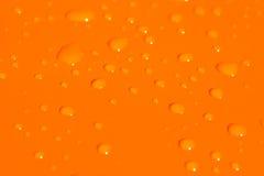 Wassertropfen auf orange Metallba Stockbilder