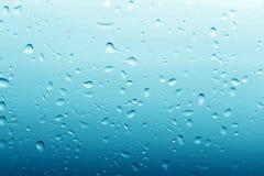 Wassertropfen auf sauberem blauem Glashintergrund Lizenzfreies Stockbild