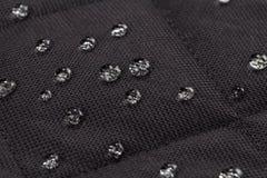 Wassertropfen auf wasserdichtem schwarzem Gewebe stockfotos