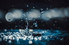 Wassertropfen, die das Glänzen fallen und spritzen stockbilder