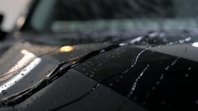 Wassertropfen fließen auf ein schwarzes Fahrzeug nach Waschanlage