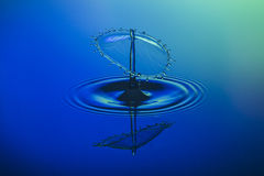 Wassertropfenzusammenstoß auf blauem Hintergrund lizenzfreies stockbild