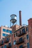 Wasserturm auf altem Backsteinbau mit Metallbalkonen Stockfotografie