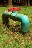 Wasserventil auf einem Grashintergrund Stockfotografie