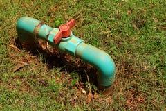 Wasserventil auf einem Grashintergrund Stockfotos