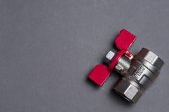 Wasserventil mit rotem Griff auf Grau Lizenzfreie Stockfotografie