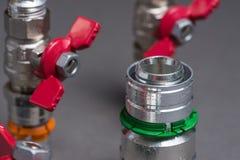 Wasserventile mit Installationen auf Grau Stockfotos