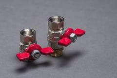 Wasserventile mit rotem Griff auf Grau Lizenzfreie Stockfotos