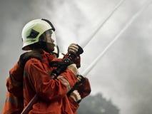 Wasserwerfertrieb vom Feuerwehrmann lizenzfreie stockbilder