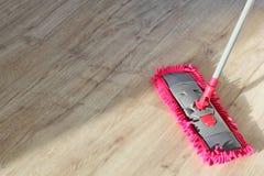 Wasstof op houten vloer met zwabber Stock Foto