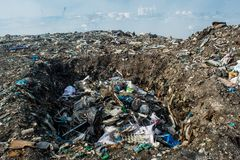 Wastage pit at the garbage dump full of smoke, litter, plastic bottles,rubbish and trash at tropical island. Wastage pit at the garbage dump full of smoke,litter Stock Image