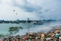 Wastage zone at the garbage dump full of smoke, litter, plastic bottles,rubbish and trash at tropical island. Wastage zone at the garbage dump full of smoke Royalty Free Stock Photography
