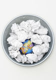 Waste bin with globe among crumpled papers view from above Stock Photos