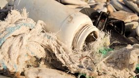 Waste bottle beach. Plastic bottle, rope and shoe discarded on shoreline stock video footage