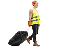 Waste collector dragging a bag of trash Stock Images