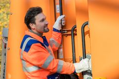Waste collector gripping handle of garbage truck Stock Photo