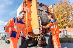 Waste collector gripping handle of garbage truck Stock Photos