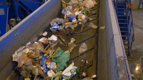 A waste conveyor transporting a large quantity of trash. Conveyor transporting a large amount of trash at waste processing plant stock footage