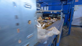 A waste conveyor transporting a lot of trash. Conveyor transporting a large amount of trash at waste processing plant stock video