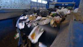 A waste conveyor transporting a lot of waste. Conveyor transporting a large amount of trash at waste processing plant stock video footage
