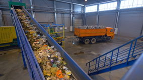 Waste on conveyor. Truck with pressed garbage. 4K. The waste is moving on the conveyor belt trough the waste disposal plant. The truck is standing with the stock video