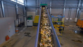 Waste disposal plant`s conveyor transporting the garbage.4K. The camera is shooting how the waste disposal plant`s conveyour is transporting the garbage stock video footage