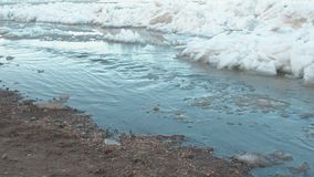 Waste is drained into the river. Sandy beach and ice on the river. stock video footage