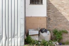 Waste beside a garage door Stock Image