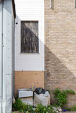 Waste beside a garage door vertical view Royalty Free Stock Images