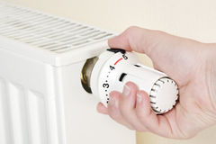 Waste of Heating costs. Close-up of a heating with hand turning thermostat in full position Stock Photos